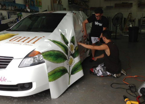 two men covering an area of a car for repainting